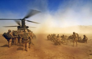 Soldiers boarding a helicopter in dusty conditions in Afghanistan.