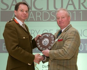 A member of the Cape Wrath Training Centre team collects the 'Heritage Project' award from Major General Nick Ashmore, at the 2011 Sanctuary Awards. (Crown Copyright)
