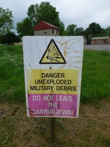 A sign warning visitors not to leave the path due to the danger of unexploded ordnance. (Crown Copyright)
