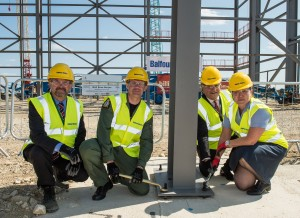 Station Commander Gp Capt Simon Edwards & Head of Establishment Gp Capt Polly Perkins put the finishing touches to first part of A400M hangar's steelwork, with Andy Duff of Balfour Beatty (l) & Airbus Military Chief Executive Richard Thompson. [Crown Copyright/MOD2015]