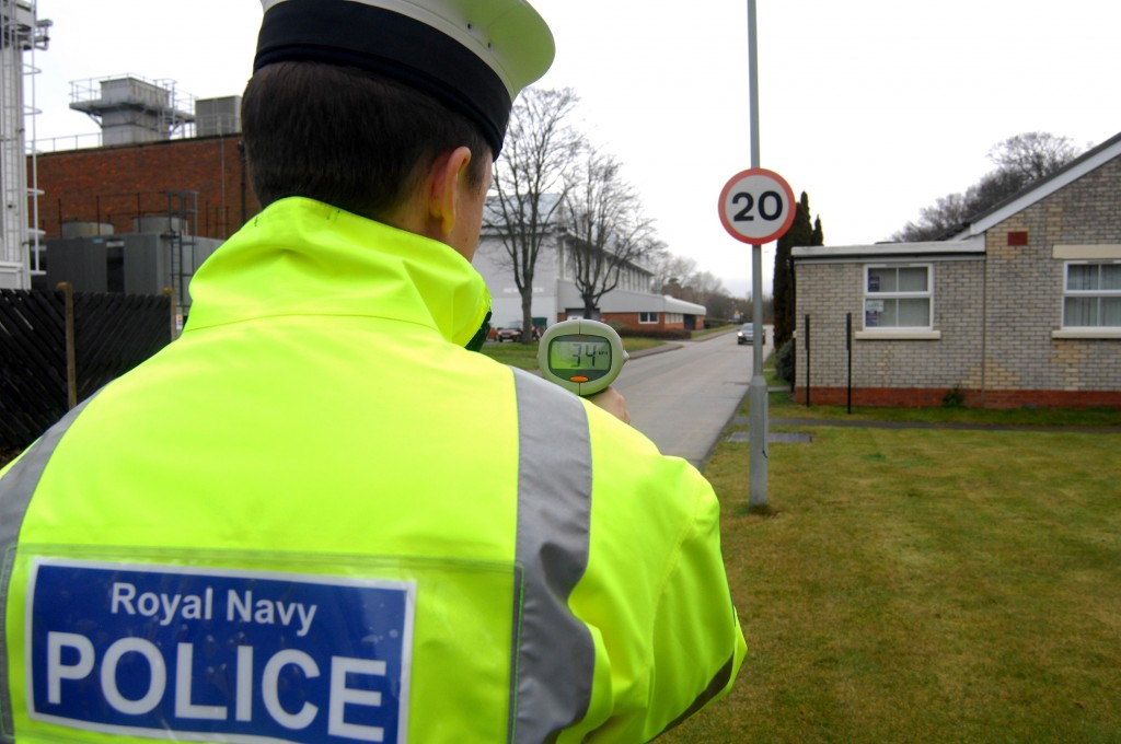 A member of the Royal Navy Police is pictured carrying out a vehicle speed check at HMS Sultan in Gosport, Hampshire.