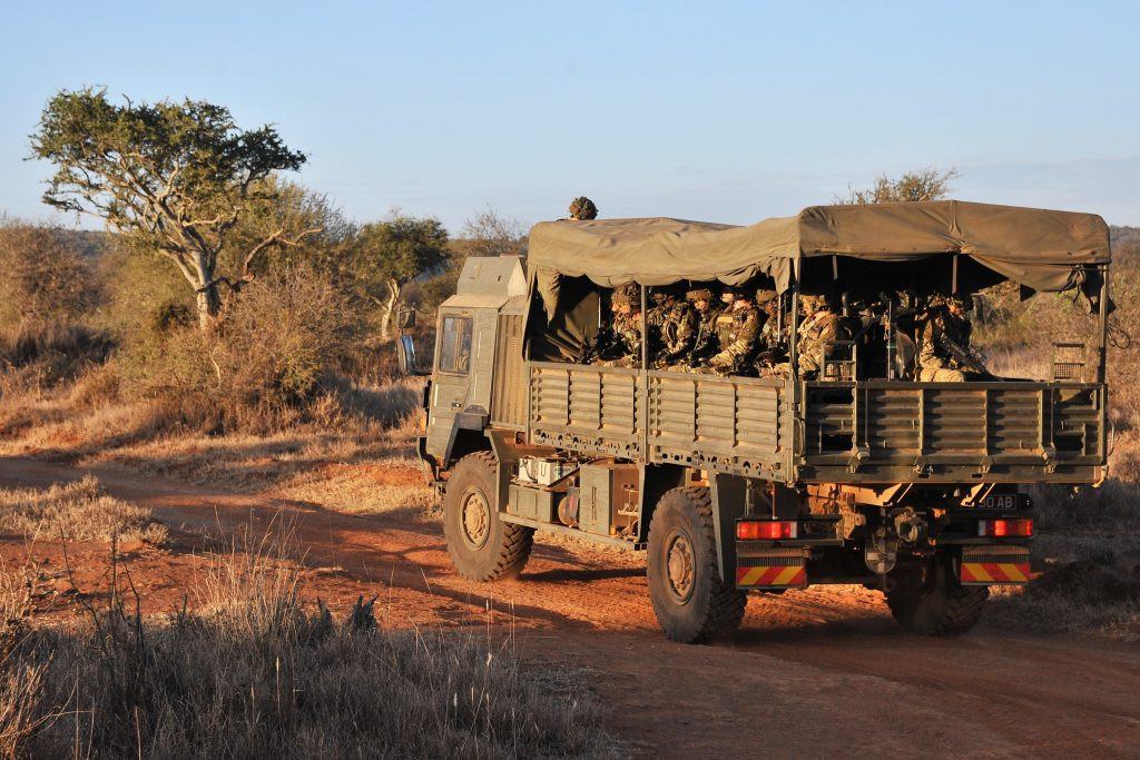 A Troop Carrying Vehicle being used to transport soldiers along a dirt road in Kenya.