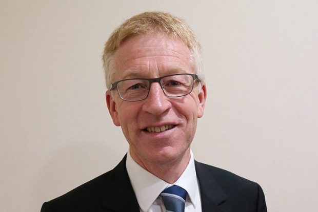 Head and shoulders image of Graham Dalton, a white man with fair hair and glasses, wearing a suit and tie. He is smiling.