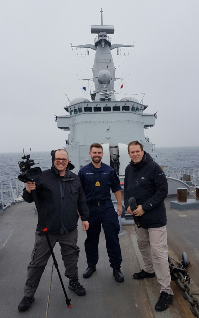 Reservist Ben Lolley on the bow of the Belgian warship BNS Louise Marie with two journalists from Crown Media [Crown Copyright, MOD 2017]