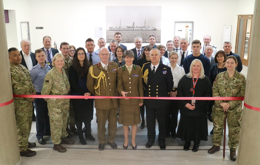 Colonel Katherine Richardson, Commanding Officer of the Royal College of Defence Medicine, cuts the ribbon to open the Glenart Castle Mess. She is accompanied by Major General Martin Bricknell, Acting Surgeon General, Surgeon Commodore Andrew Hughes, Commander Defence Medical Group, and representatives from the Surgeon General's Headquarters, DIO, and others. [Crown Copyright/MOD2017]