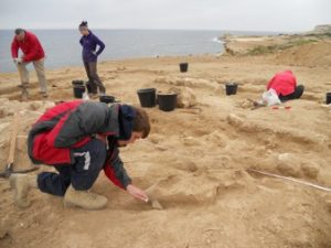 The team excavating an Amphora in a Roman building at Dreamer's Bay. Note the wet weather clothing….it isn't always hot in Cyprus! [Crown Copyright, MOD 2017]