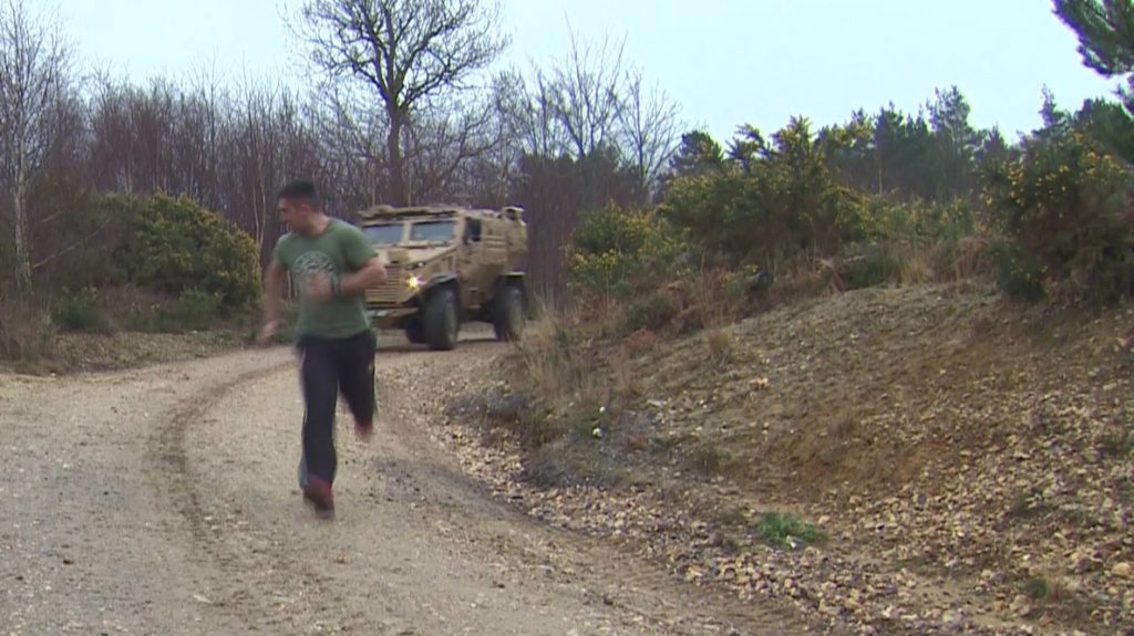 A runner is surprised by a Foxhound armoured vehicle when running on the training estate. [Crown Copyright, MOD]
