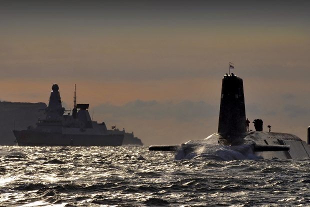 Nuclear submarine HMS Vanguard, above the surface, with HMS Dragon in the background. [Crown Copyright, MOD]