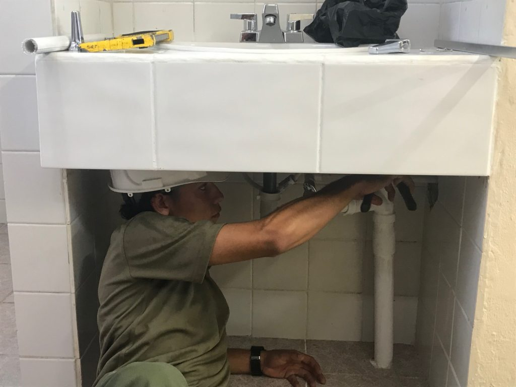 A LEC from Belize working on some plumbing. [Crown Copyright]