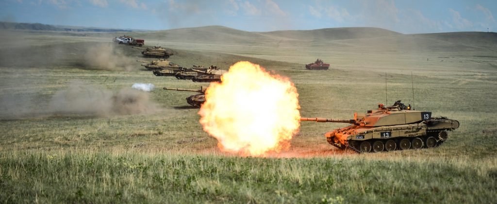 A line of Challenger 2's fire as part of the Royal Welsh Battle Group during Exercise Prairie Lightning at BATUS in 2012. [Crown Copyright/MOD2012]