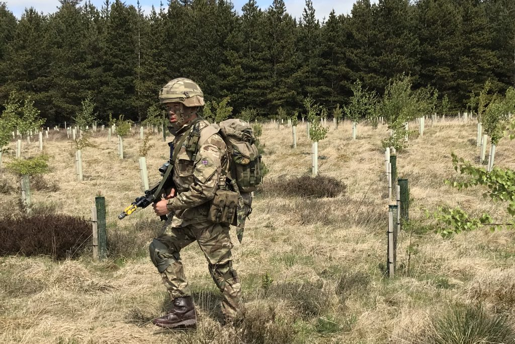 A Gurkha recruit, in full uniform including helmet and body armour, and carrying his weapon and a bergen, moves through an area of growing trees with a mature copse in the background.