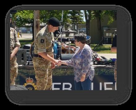 Josephine Deneve receiving her Commander's Coin from BATUS Commander Col. Marcus Evans. [Crown Copyright/MOD]