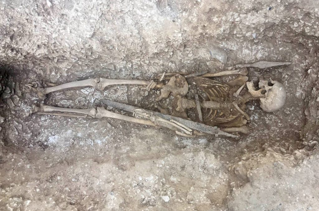 The skeleton of a Saxon warrior in an excavated grave, with a sword and spear.