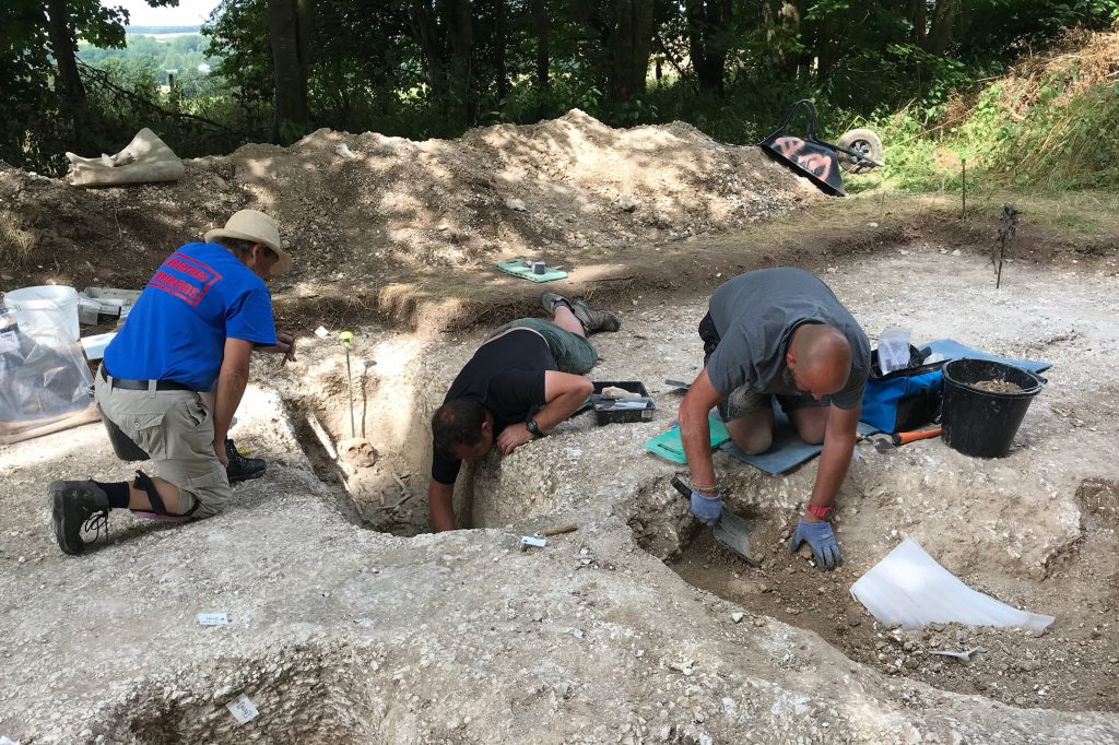 Three participants kneeling on the end of an archaeological trench. Two are digging, one is observing.