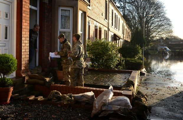 Two soldiers from 2 LANCS speaking to a homeowner in a flooded street.