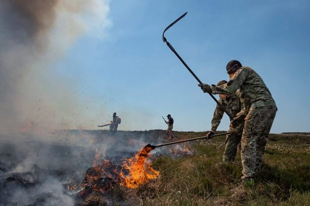 In the foreground, a soldier from 4 SCOTS holds a long implement in the air, in the middle of using it to beat down flames in the centre of the image. In the background are other soldiers.
