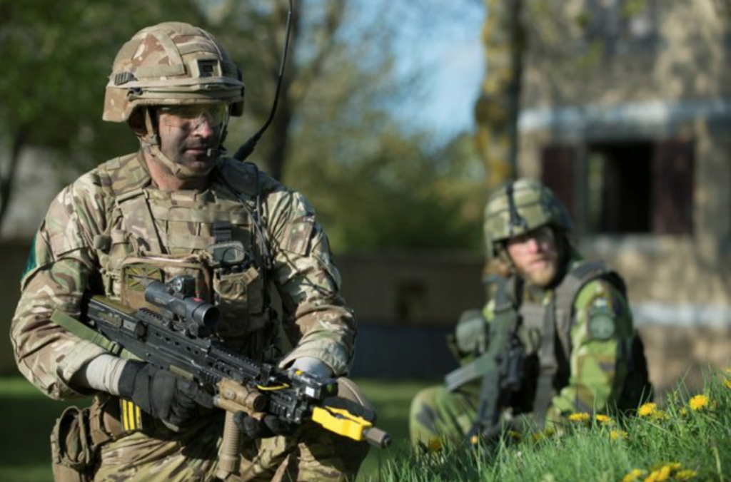 A British soldier in the foreground and a Swedish soldier in the background, in front of a brick building at Copehill Down urban training area.