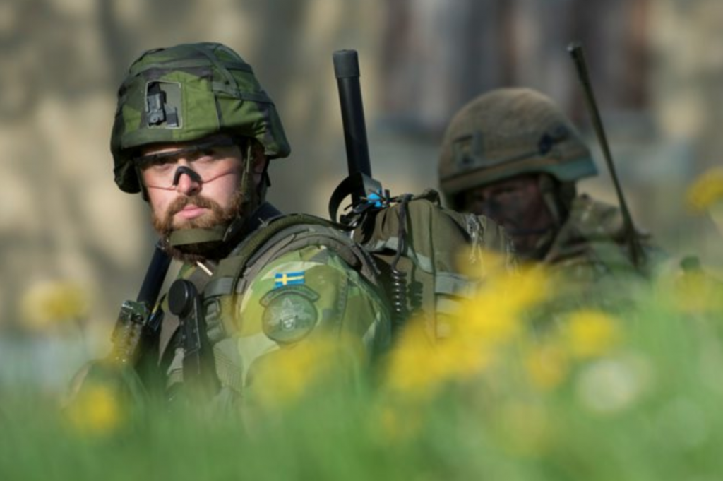A Swedish soldier, in uniform and standing in profile, is looking towards the camera, with a British soldier behind him.