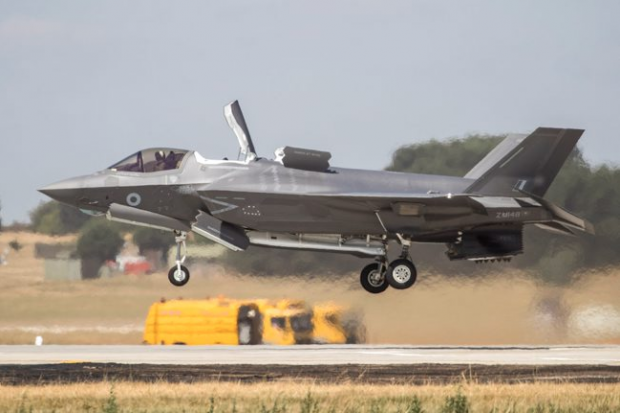 An F-35 landing vertically onto a new landing pad at RAF Marham. The aircraft is a few feet above the ground.