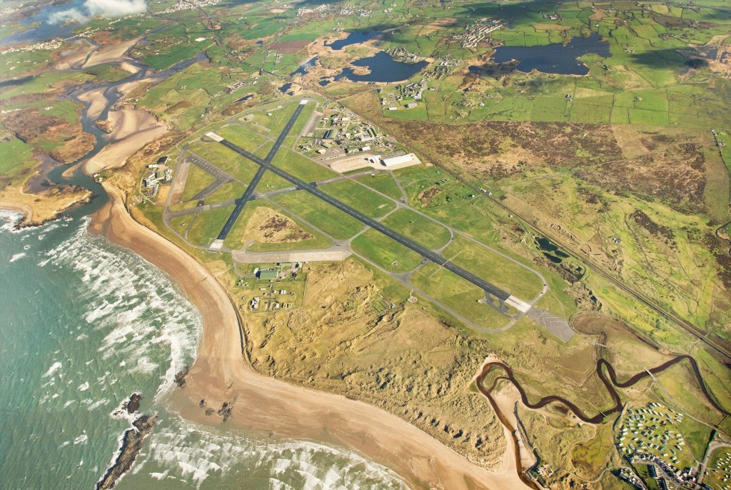 An aerial view of RAF Valley, with the beach and two runways in particular very visible.
