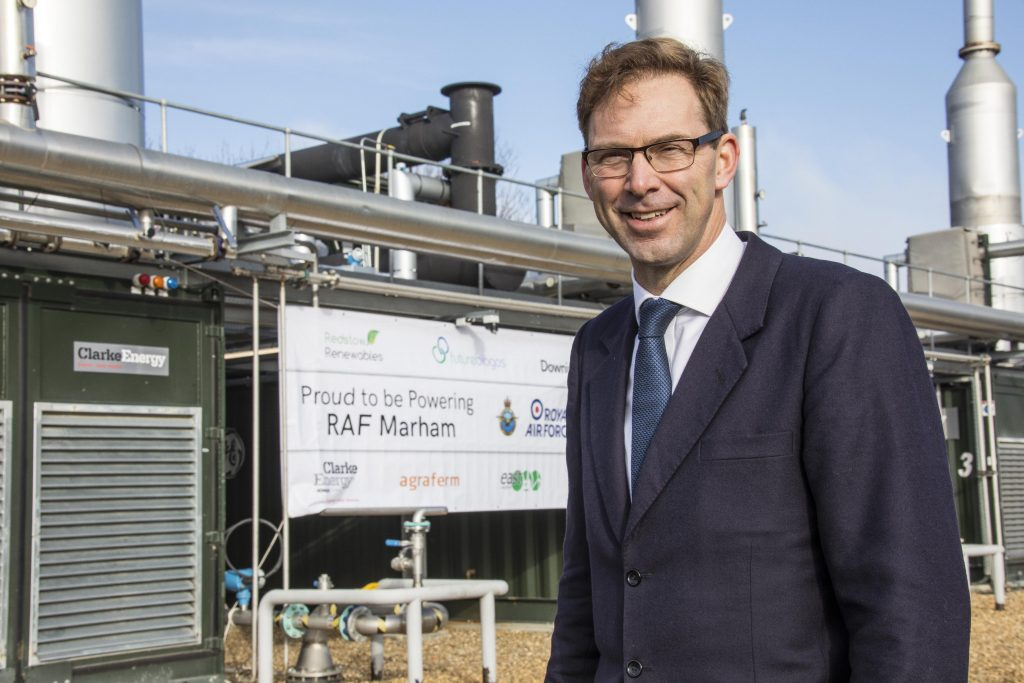 "Tobias Ellwood MP standing at the biogas plant, in front of a sign which reads ""Proud to be powering RAF Marham""."