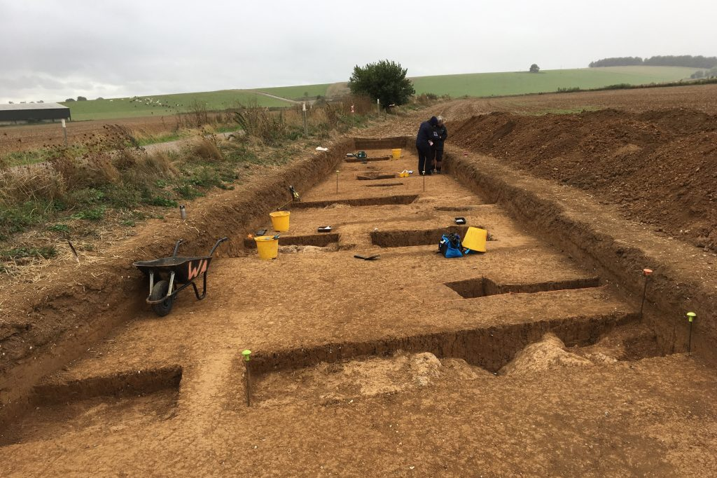 A wide, shallow trench with a number of deeper trenches within it. There is a wheelbarrow and several buckets and two people at the far end conversing.