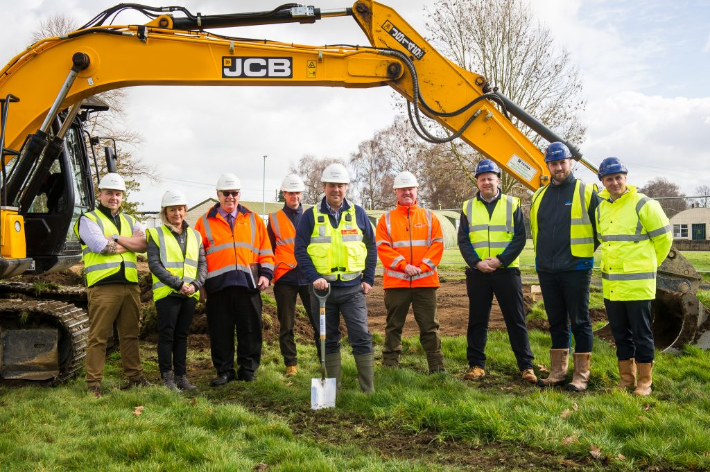 Representatives of DIO, Landmarc and Pave Aways Ltd attend the ground breaking ceremony. They are all dressed in helmets and high vis jackets and one holds a spade. They are standing on grass in front of a building.