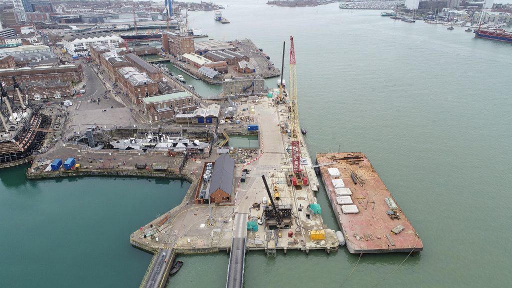 A aerial view of construction work taking place at HMNB Portsmouth. Image shows the sea, cranes and buildings.