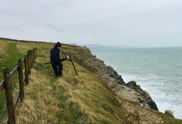 Keri Thomas, from the Environmental and Ordnance Liability team at DIO carrying out a check with a piece of equipment on the cliff edge of the South West Coast Path Trail in Dorset. She is standing on grass at the edge of the cliff with a sea view.