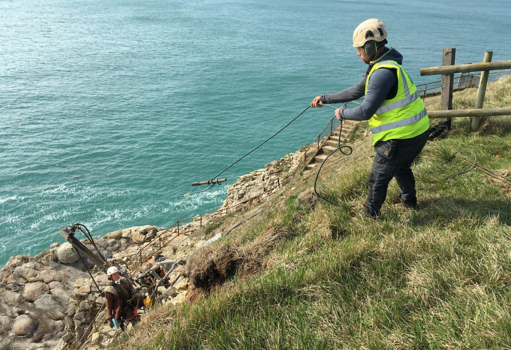 A member of the Vertical Technologies team, dressed in a helmet and reflective jacket swings a rope down the cliff to a colleague.