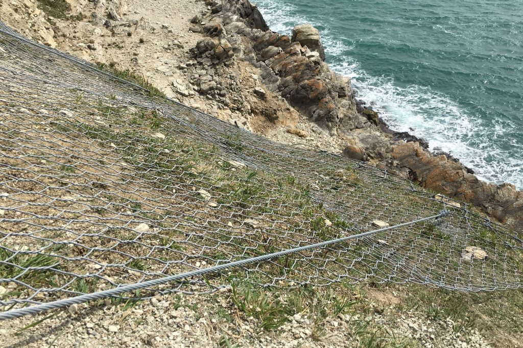 The image shows metal netting over the rocks. It is taken from the top of a steep slope looking down towards the sea.