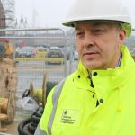 Project Manager, Colin Efford is pictured in a hi-vis jacket and helmet. Behind him is construction work taking place at HMNB Portsmouth