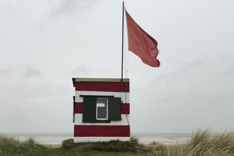 In the foreground is a shallow grassy slope and behind appears to be the beach. In the centre of the image is a small building with red and white horizontal stripes and a large red flag.