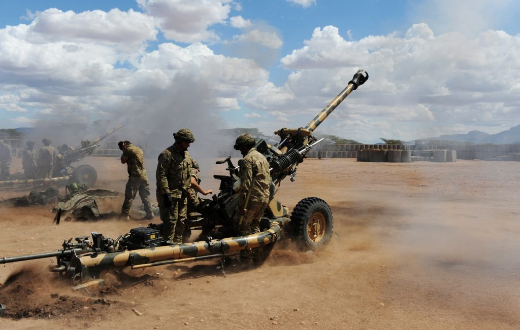 Soldiers from 4 RIFLES firing artillery on exercise in Kenya. The ground is red and dusty.