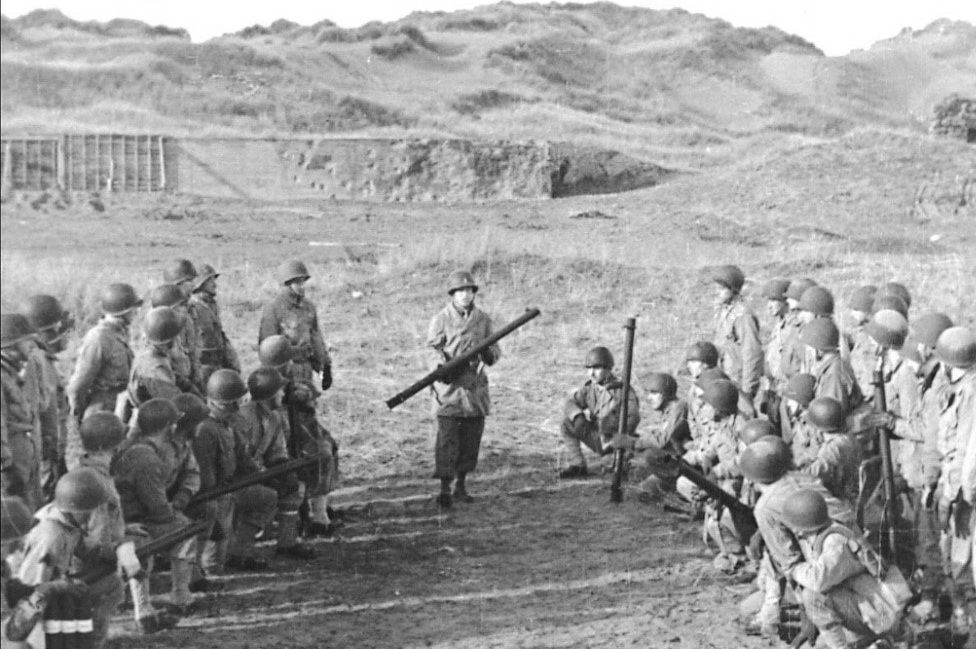 A black and white image of US troops armed with bazookas. They are gathered in two groups, one on each side of the picture, all looking towards one man in the middle holding a bazooka. Behind them is the concrete wall at Braunton Burrows.