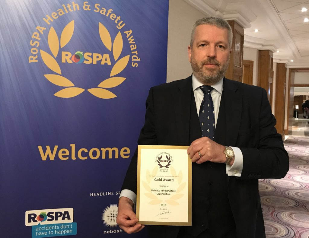 Paul Wilson holding the RoSPA Gold Award certificate in front of a RoSPA banner.