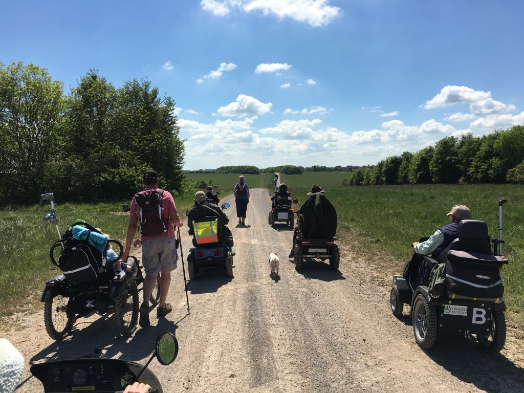 Five members from the Disabled Ramblers on a pathway on the Salisbury Plain Training Area. Around the paths are trees and it is a sunny day.