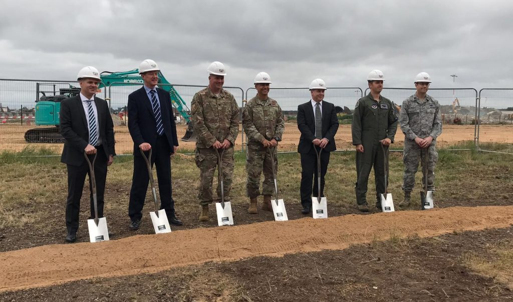 7 men including representatives from DIO and Kier VolkerFitzPatrick hold spades are in white helmets standing next to a line of sand for the ground breaking ceremony at RAF Lakenheath.