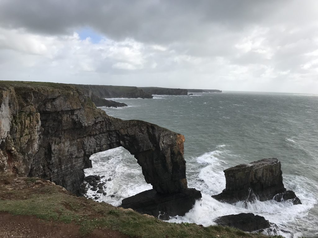A picture of a the green bridge of Wales at the Castlemartin Ranges. There is sea overlooking the bridge.