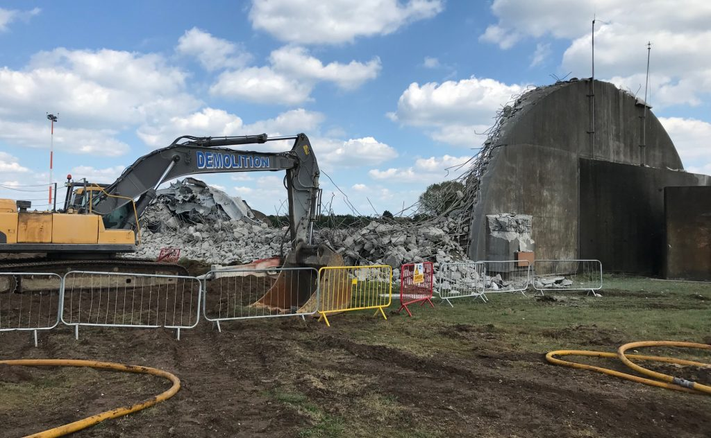 A hangar at RAF Lakenheath is being demolished with a vehicle. There are materials from the demolished hangar and rubble pictured next to the remaining building.