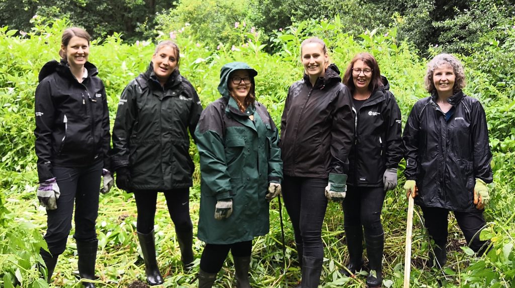 6 volunteers in black jackets and trousers pictured infront of large green plants
