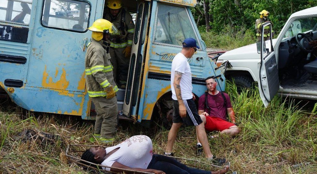 Pictured is a light blue tourist bus with two members of the Belize Defence Force next to it. A casulty is infront of the bus and another casulty is lying down on grass. A vehicle is also pictured next to the bus.