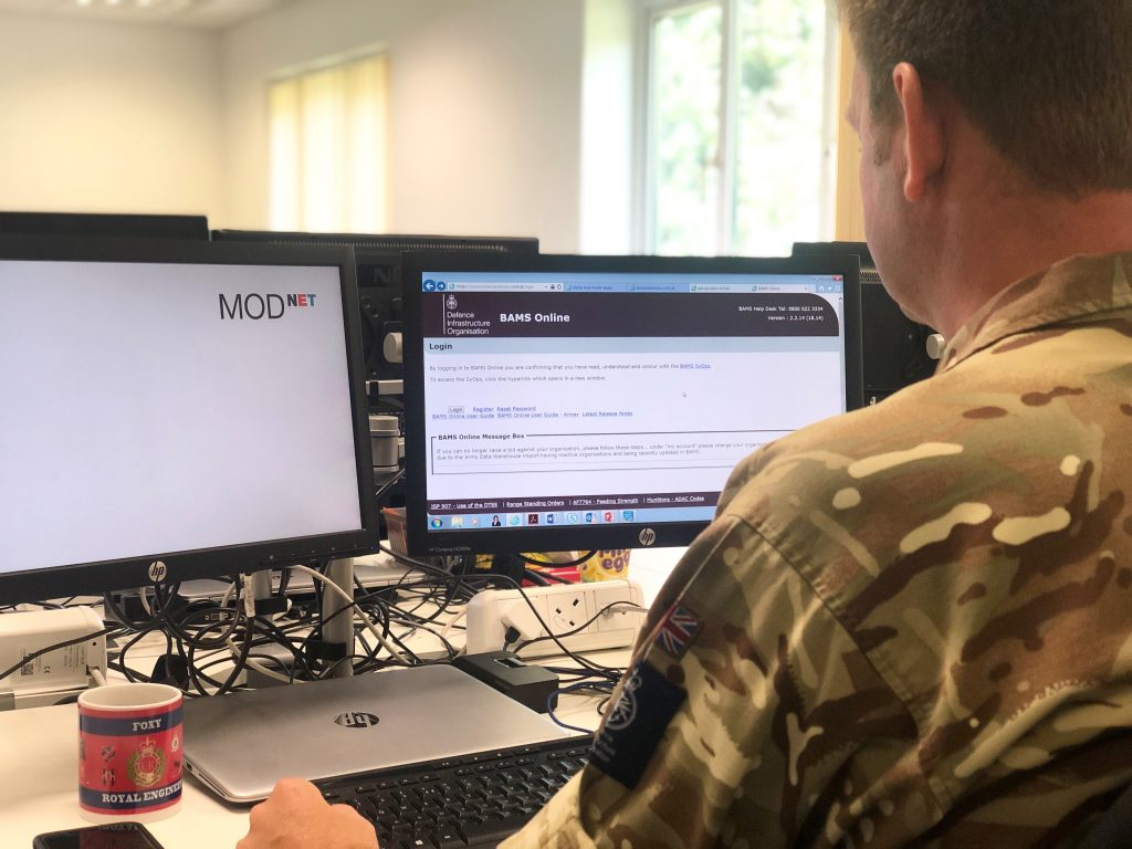 Image of service personnel wearing his army uniform facing two computer screens. One computer screen on the right-hand side shows the BAMS online website and the left-hand side screen shows a blank white screen with MOD net on the top right-hand corner.