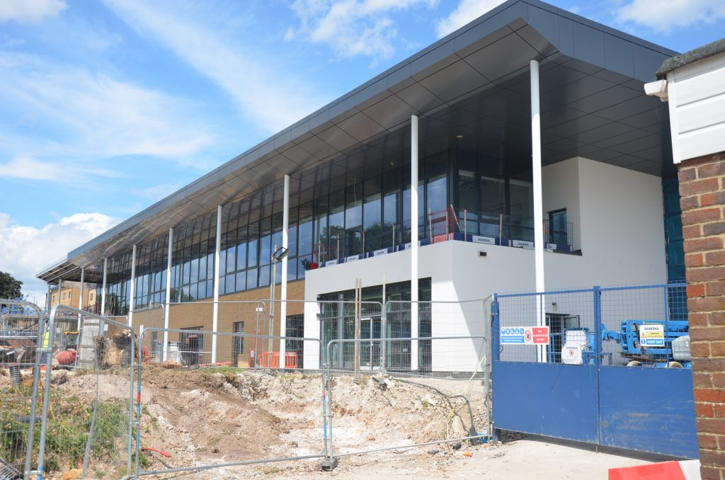 Pictured is a white and grey building with several windows under construction. The building is a new officers' and senior commissioned officers' combined mess at Worthy Down. There is grey fencing infront of the building and soil