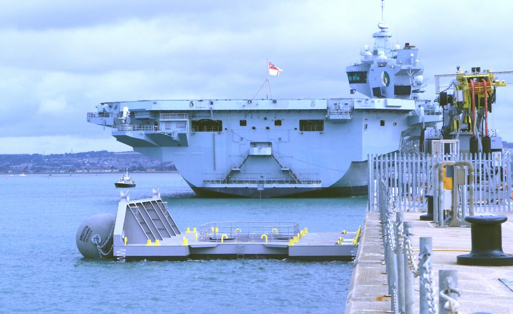 HMS Queen Elizabeth is parked next to sea wall at Portsmouth. A grey Fendered Spacer Unit is located near by.