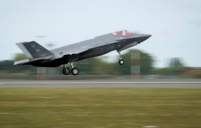 Pictured is an F35 taking off on a runway. The F35 is grey with 3 wheels. There is a little window at the front where you can see the pilot. There is grass next to the runway
