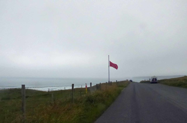 A red flag is located on some grass and fencing near a road. There is sea behind the grass.