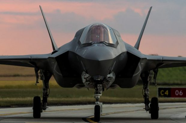 An F-35 jet, facing the camera and on the runway.