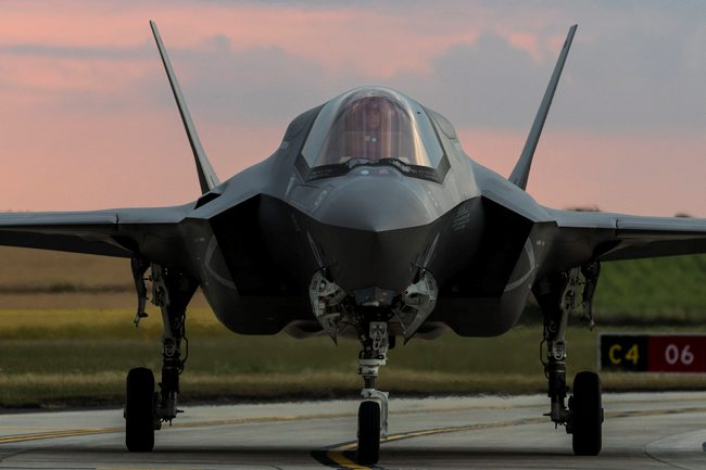 Pictured is an F35 Lightning jet. The Jet is facing the front and is grey with a window at the front and 3 wheels, one at the front and two at the back.It has two grey wings at the back and is pictured on a road with a field behind it. The sky is pink/blue.