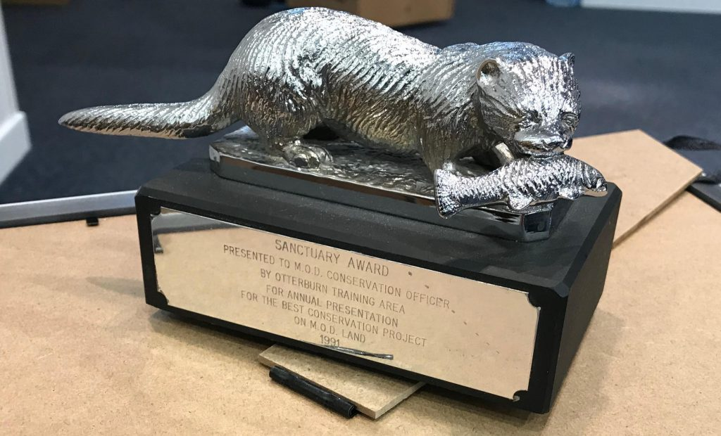 Picture of a silver and black award. The award is a black block with silver writing stating the Sanctuary Award and the top of the block has a Silver Otter on it with a silver fish in it's mouth.